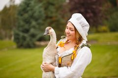有一只鹅的一名农民妇女在她的在草甸中的胳膊 图库摄影