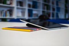 有一只黑屏和五颜六色的蜡笔的片剂在书桌选项 库存照片