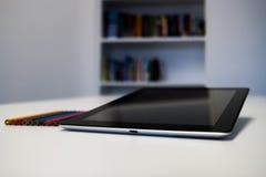 有一只黑屏和五颜六色的蜡笔的片剂在书桌选项 库存图片