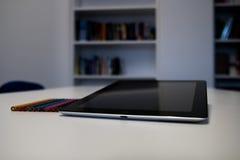 有一只黑屏和五颜六色的蜡笔的片剂在书桌tabl 库存照片
