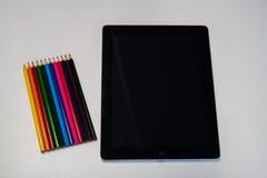 有一只黑屏和五颜六色的蜡笔的片剂在白色de 库存图片