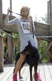 有一只黑短毛猎犬的白肤金发的妇女尾随户外 图库摄影