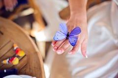 有一只紫色蝴蝶的新娘的手 免版税图库摄影