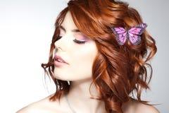 有一只蝴蝶的俏丽的妇女在她的红色头发-秀丽射击 免版税库存图片