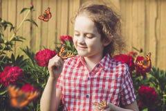 有一只蝴蝶的卷曲女孩在他的手指 图库摄影