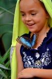 有一只蝴蝶的小女孩在她的衬衣 库存图片