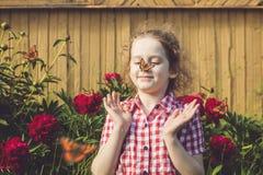 有一只蝴蝶的小女孩在他的鼻子 图库摄影
