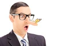 有一只蝴蝶的惊奇的人在他的鼻子 免版税库存照片