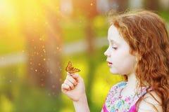 有一只蝴蝶的惊奇的卷曲女孩在他的手指 免版税库存图片