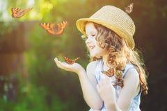 有一只蝴蝶的笑的小女孩在他的手上 愉快的childho 免版税库存照片