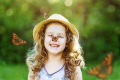 有一只蝴蝶的笑的小女孩在他的鼻子 免版税图库摄影