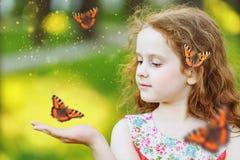 有一只蝴蝶的美丽的卷曲女孩在他的头发 免版税库存照片