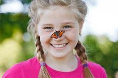 有一只蝴蝶的美丽的女孩在她的鼻子 库存图片