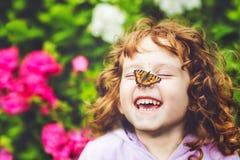 有一只蝴蝶的美丽的小女孩在他的鼻子 免版税库存照片