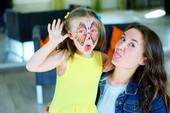 有一只蝴蝶的面孔绘画的俏丽的女孩与保姆的 免版税库存图片