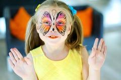 有一只蝴蝶的面孔绘画的俏丽的女孩在黄色礼服的 免版税库存照片