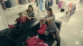 有一可爱宝贝的年轻美丽的母亲在尝试在镜子前面的衣裳的商店 影视素材