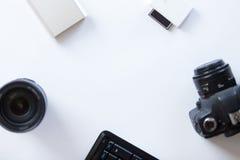 有一台专业照相机和accessoires的白色书桌 免版税库存照片