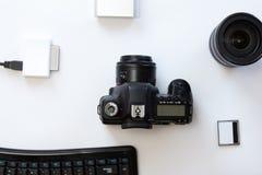 有一台专业照相机和accessoires的白色书桌 免版税库存图片
