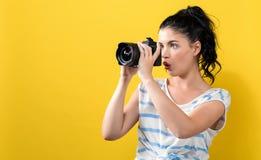 有一台专业照相机的年轻女人 图库摄影
