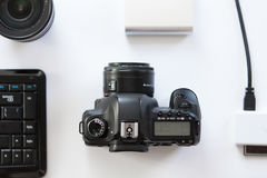 有一台专业照相机的白色对此的书桌和accessoires 库存图片