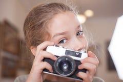 有一台减速火箭的照相机的女孩做一张照片 免版税库存图片