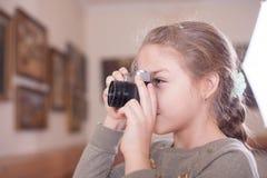 有一台减速火箭的照相机的女孩做一张照片 图库摄影