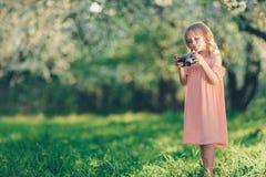 有一台减速火箭的照相机的小女孩在公园 库存照片