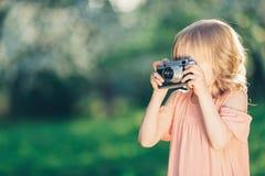有一台减速火箭的照相机的小女孩 免版税图库摄影