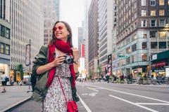 有一台减速火箭的照相机的愉快的女孩在街道上 图库摄影