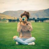 有一台减速火箭的照相机的年轻妇女 图库摄影