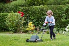 有一台割草机的小男孩在庭院里 库存照片