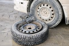 有一台压缩机的一个轮子在一条肮脏的路的一辆老汽车附近 库存图片