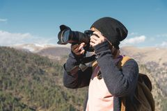 有一台数字式SLR照相机的拍摄在山的一个白肤金发的女孩的特写镜头画象 时髦的自由职业者 图库摄影