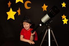 有一台望远镜的愉快的男孩在黑背景 图库摄影