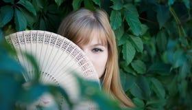 有一台木风扇的害羞的女孩 免版税库存照片