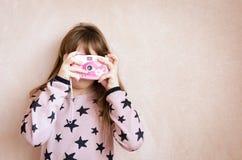 有一台桃红色照片照相机的小女孩 库存照片