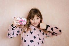 有一台桃红色照片照相机的小女孩 免版税库存图片