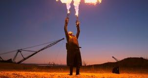 有一台火焰喷射器的一个人在慢动作的日落 服装为蛇神默示录和万圣节 股票视频
