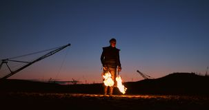 有一台火焰喷射器的一个人在慢动作的日落 服装为蛇神默示录和万圣节 股票录像