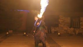 有一台火焰喷射器的艺术家在他的在表现期间的手上 Fireshow 股票视频