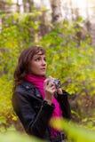 有一台照片照相机的深色的妇女在秋天公园 免版税库存图片