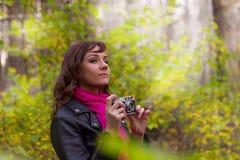 有一台照片照相机的深色的妇女在秋天公园 免版税图库摄影
