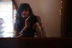 有一台照相机的一个女孩在镜子 免版税库存照片