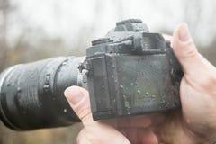 有一台照相机的一位摄影师在雨中 免版税图库摄影