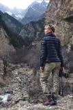 有一台照相机的一位美丽的女孩摄影师在山 免版税库存照片