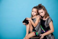 有一台照相机的两个女孩在照片写真 库存图片