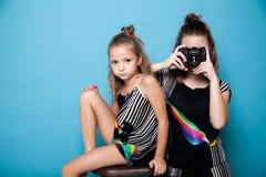 有一台照相机的两个女孩在照片写真 免版税库存照片