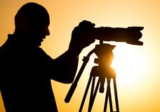 有一台照相机的人摄影师在日落 库存图片