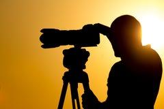 有一台照相机的人摄影师在日落 图库摄影